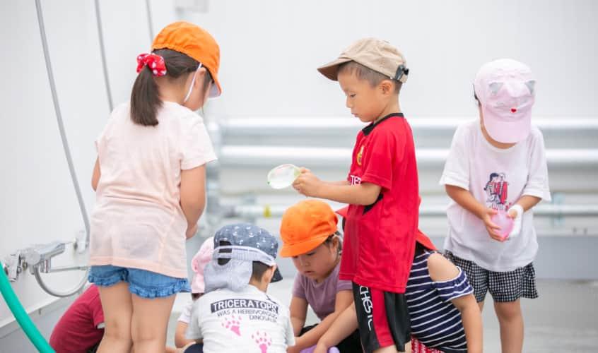 水場の周りに集まって遊んでいる子どもたち