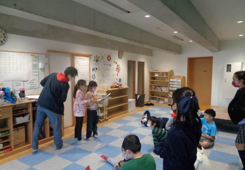 机に向かって勉強している子どもたちと教えている先生