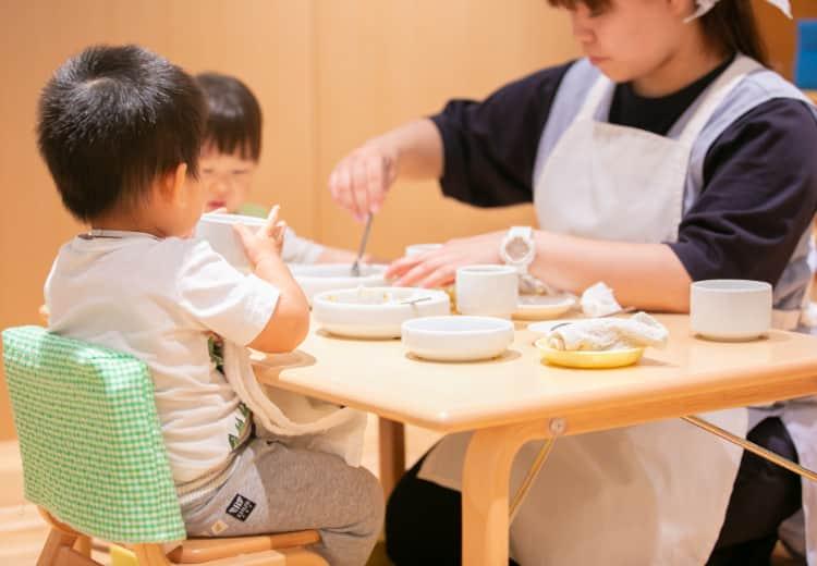 保育士の介助をうけながら食事をする子どもたち