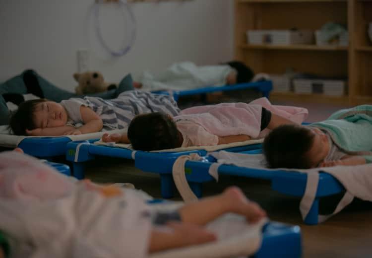 暗い室内で昼寝をしている子どもたち